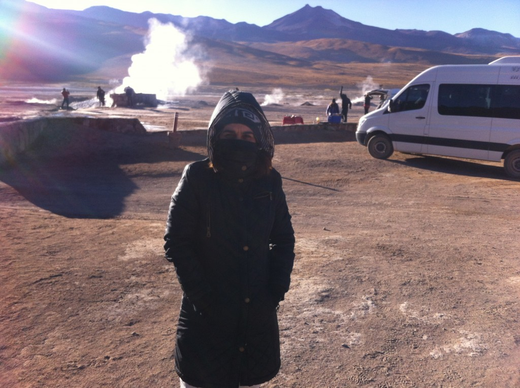 Minha mãe com frio com os Gêiseres do Atacama ao fundo.